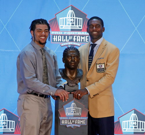 b0145f0a9a388f Former NFL player Randy Moss, right, poses with a bust of himself and  presenter, son Thaddeus Moss, during an induction ceremony at the Pro  Football Hall of ...